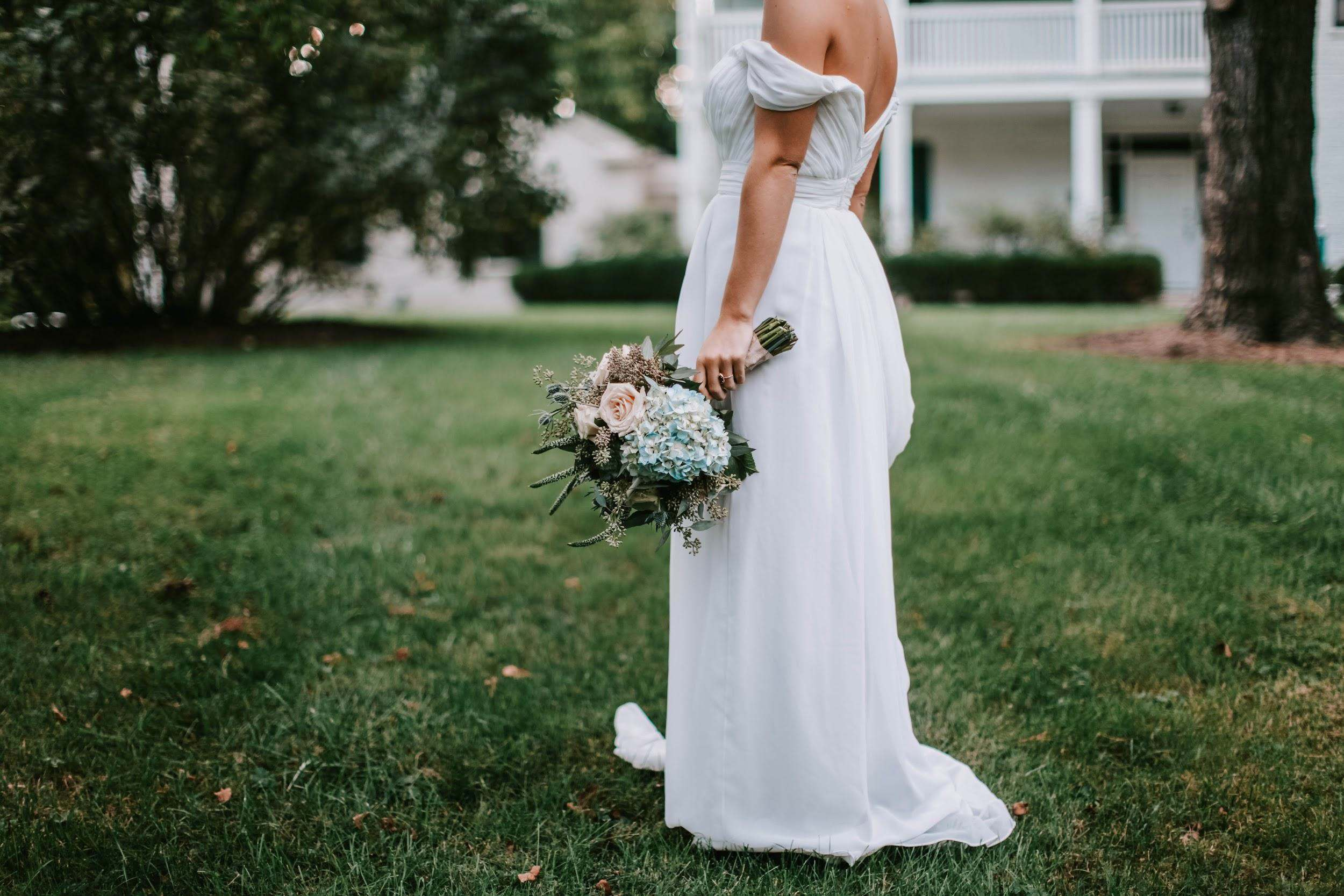 A Bride in an Off-Shoulder Wedding Dresses on the Grass