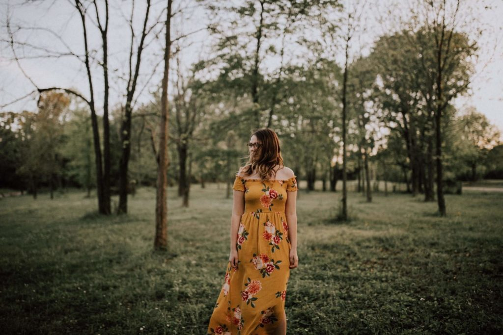 A woman wears maxi dress in the forest